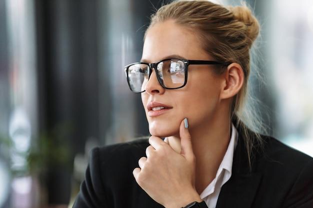 Mujer de negocios serio sentado en la cafetería mirando a un lado.