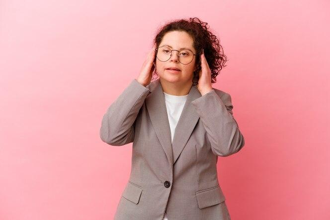 mujer de negocios con síndrome de down aislado en la pared rosa que cubre las orejas con las manos