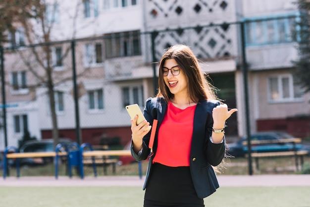 Mujer de negocios con smartphone al aire libre