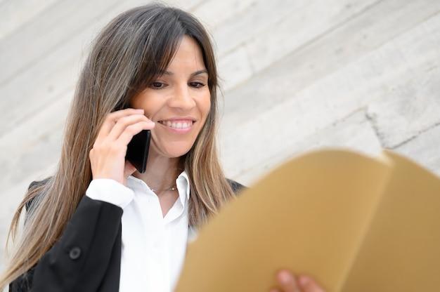 Mujer de negocios sonriendo, sosteniendo documentos en sus manos. foto de alta calidad