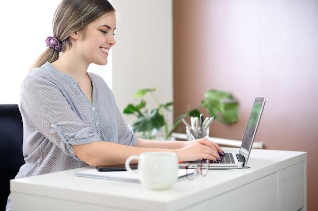 Mujer de negocios sonriendo, usando la computadora en casa, oficina. foto de alta calidad