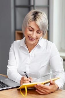 Mujer de negocios sonriente escribiendo en agenda