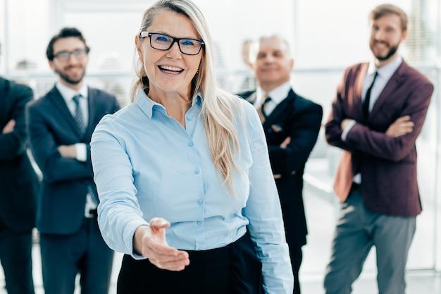 Mujer de negocios sonriente extendiendo su mano para un apretón de manos
