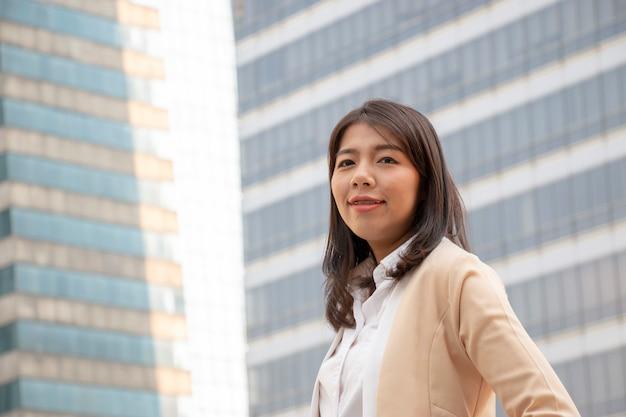 Una mujer de negocios sonriente con el fondo del edificio.