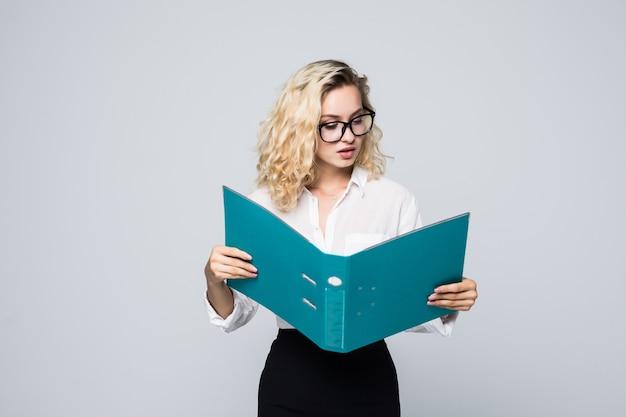 Mujer de negocios sonriente leyendo contratos de una carpeta aislada en la pared blanca