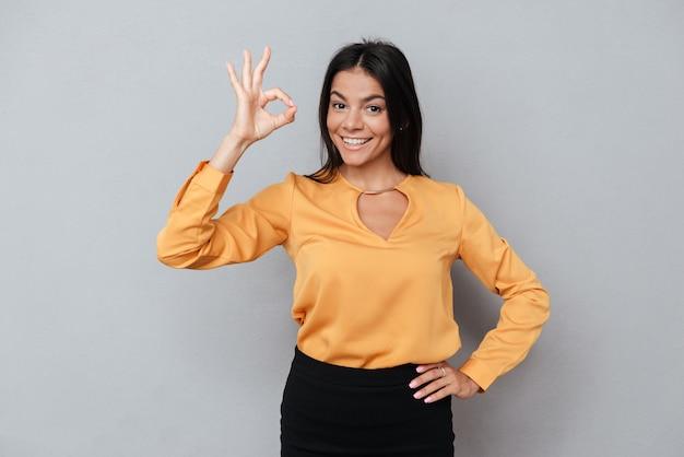Mujer de negocios sonriente mostrando gesto bien y mirando a cámara