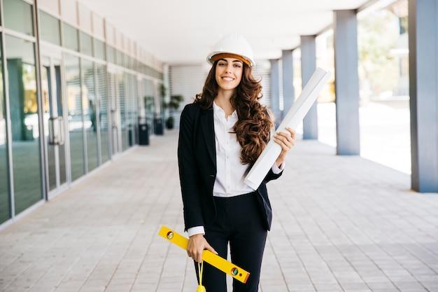 Mujer de negocios sonriente con plano y nivel