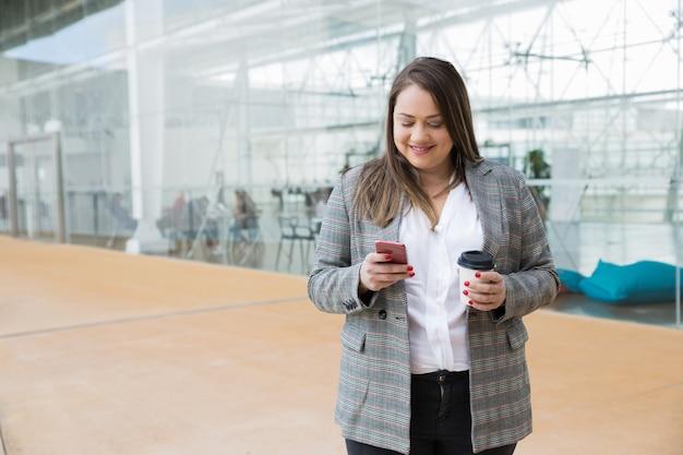 Mujer de negocios sonriente que manda un sms en smartphone al aire libre