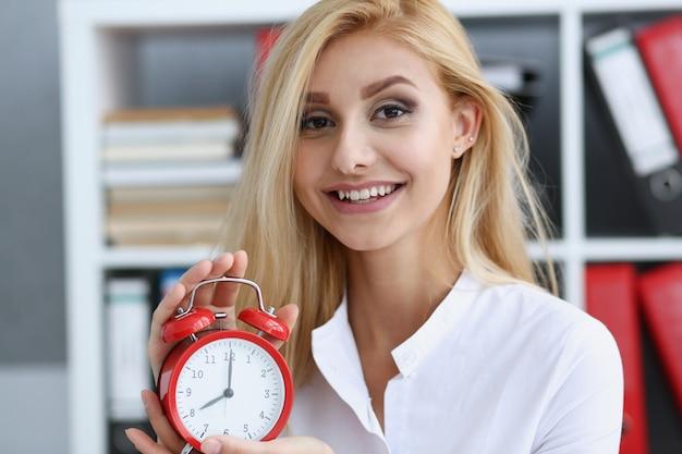 Mujer de negocios sonriente que sostiene el reloj disponible