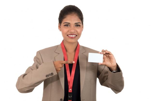 Mujer de negocios sonriente que sostiene una tarjeta de visita o una tarjeta de identificación en blanco