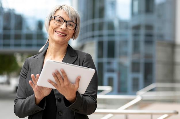 Mujer de negocios sonriente que usa la tableta