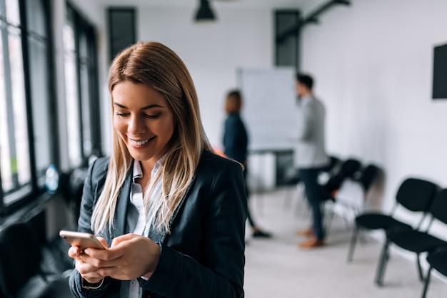Mujer de negocios sonriente que usa el teléfono durante una rotura. colegas de pie en el fondo