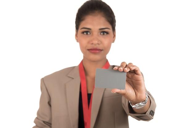 Mujer de negocios sonriente sosteniendo una tarjeta de presentación en blanco o tarjeta de identificación sobre fondo blanco.