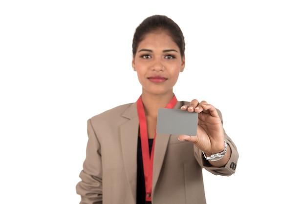 Mujer de negocios sonriente sosteniendo una tarjeta de presentación en blanco o una tarjeta de identificación
