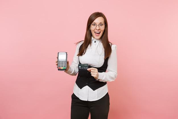 Mujer de negocios sorprendida joven que sostiene la terminal de pago del banco moderno inalámbrico para procesar y adquirir pagos con tarjeta de crédito, tarjeta negra aislada en fondo rosa. jefa. riqueza de carrera de logro.