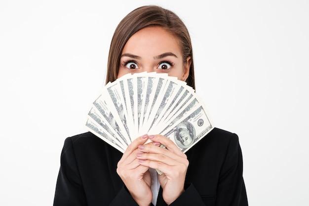 Mujer de negocios sorprendida que cubre la cara con dinero