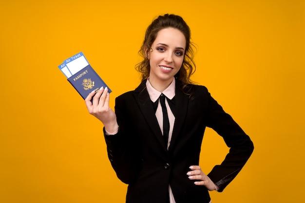 Mujer de negocios sosteniendo billetes y pasaporte sobre fondo amarillo studio