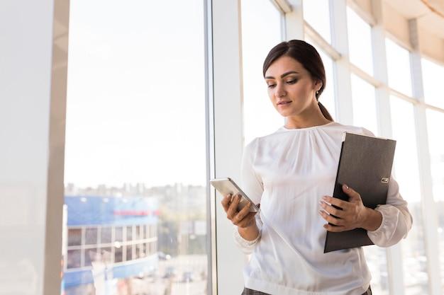 Mujer de negocios sosteniendo la carpeta y mirando el teléfono inteligente