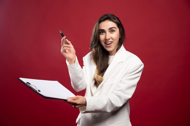 Mujer de negocios sosteniendo un cuaderno abierto