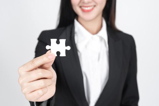 Mujer de negocios sosteniendo y mostrando un rompecabezas