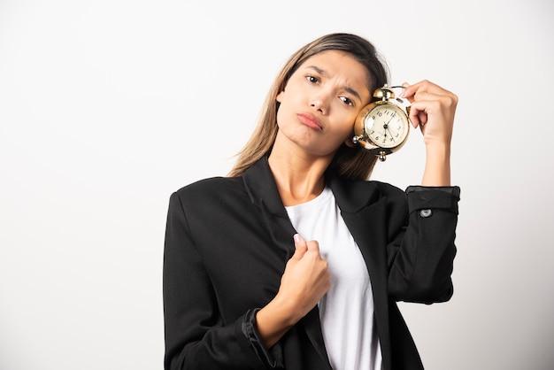 Mujer de negocios sosteniendo un reloj de alarma en la pared blanca.