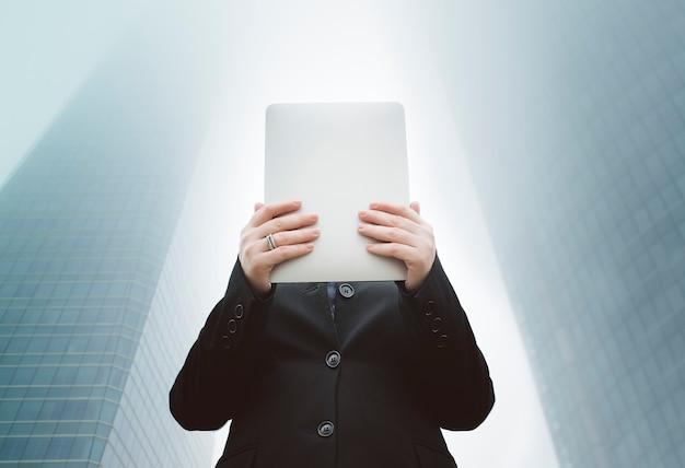 Mujer de negocios sosteniendo su mesa entre dos rascacielos en un día brumoso
