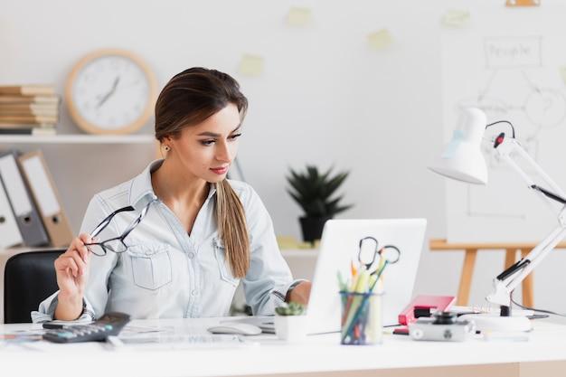 Mujer de negocios sosteniendo sus gafas y trabajando en la computadora portátil
