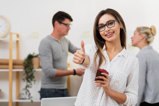 Mujer de negocios sosteniendo una taza de café y mostrando signo ok