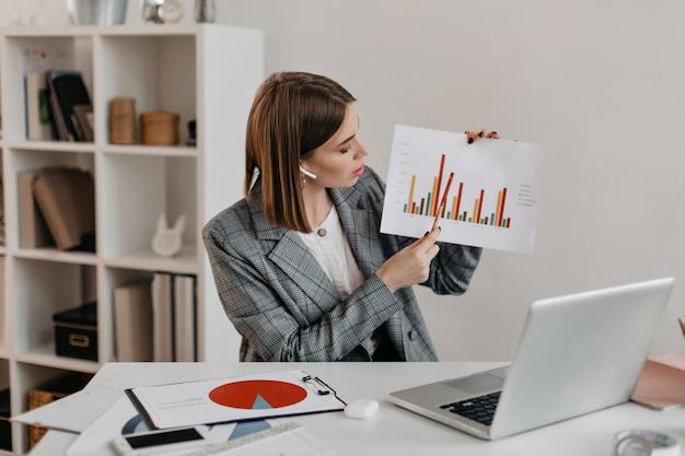 La mujer de negocios sostiene el gráfico en sus manos y se lo cuenta a los clientes a través de la comunicación por video mientras está sentada en un lugar de trabajo brillante.