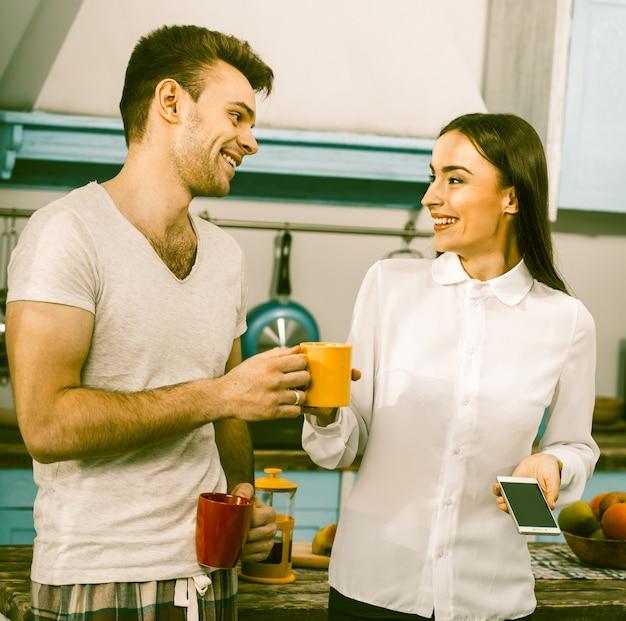 Mujer de negocios con su esposo en pijama se ríe de la cocina