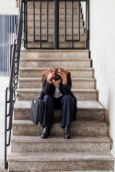 Mujer de negocios subrayada que se sienta en las escaleras