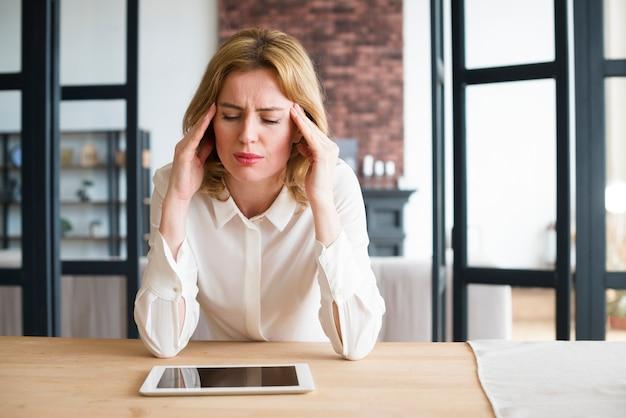Mujer de negocios subrayada que se sienta en la tabla con la tableta