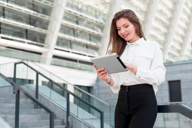 Mujer de negocios con una tablet en la calle