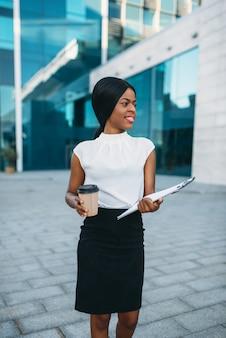 Mujer de negocios con taza de café y bloc de notas