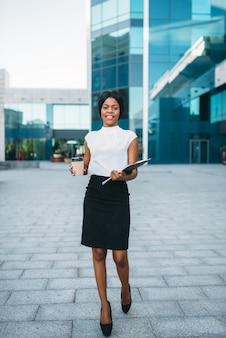 Mujer de negocios con taza de café de cartón y bloc de notas al aire libre