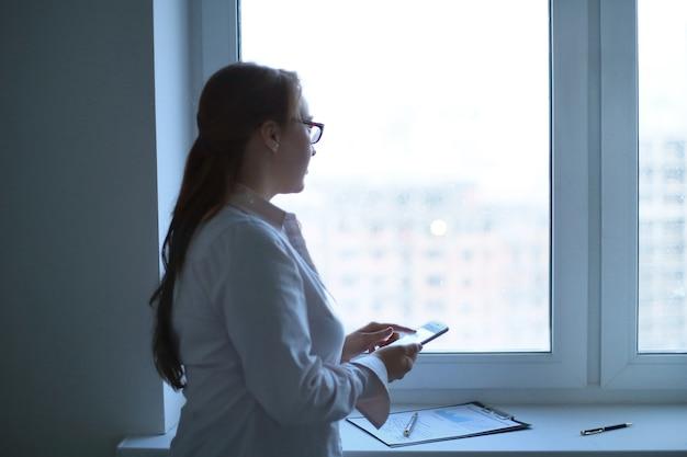 Mujer de negocios con un teléfono inteligente mientras está de pie cerca de una ventana de la oficina concepto de negocio.