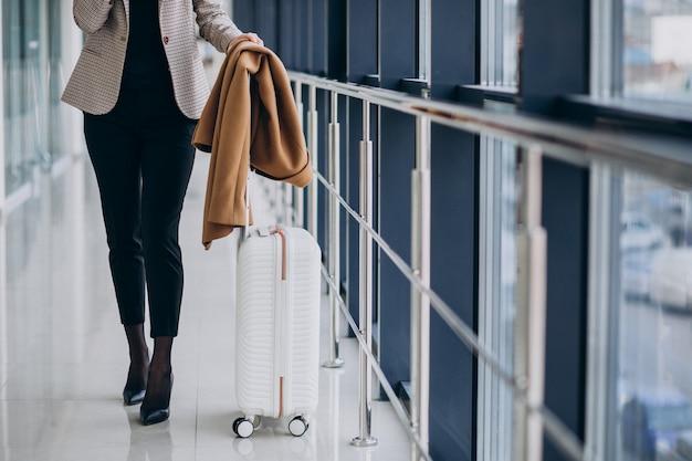 Mujer de negocios en terminal con bolsa de viaje