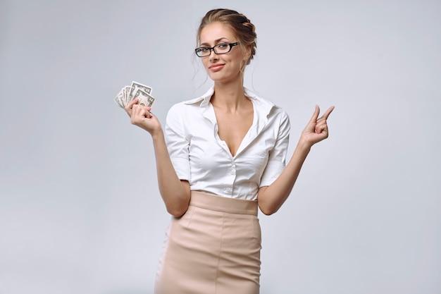 Una mujer de negocios tiene un poco de dinero en su mano derecha.