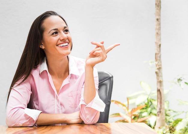 Mujer de negocios de tiro medio apuntando en una dirección