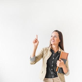 Mujer de negocios del tiro medio que señala con el espacio de la copia