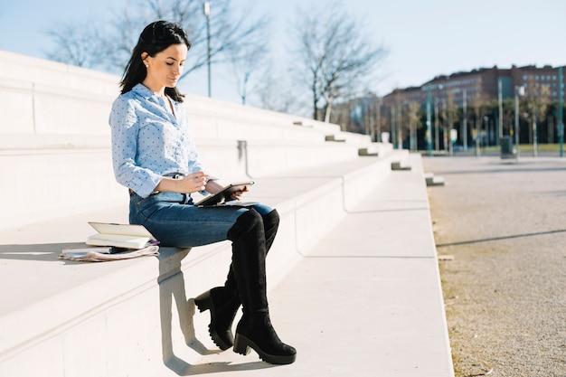 Mujer de negocios trabajando al aire libre con tableta