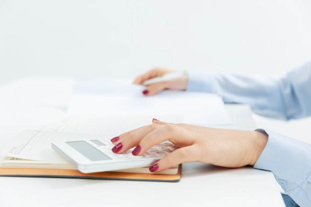 Mujer de negocios trabajando con una calculadora con un fondo blanco.