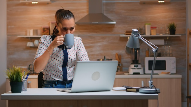 Mujer de negocios trabajando desde casa por la noche escribiendo en la computadora portátil y tomando café. empleado enfocado ocupado que usa la red inalámbrica de tecnología moderna haciendo horas extras para leer el trabajo, escribir, buscar