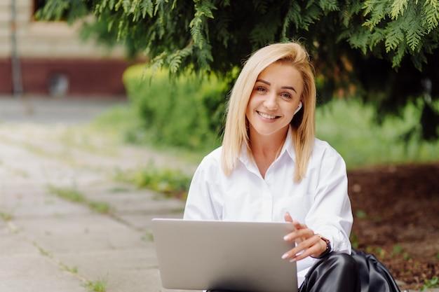 Mujer de negocios trabajando en la computadora portátil afuera en el parque de la ciudad