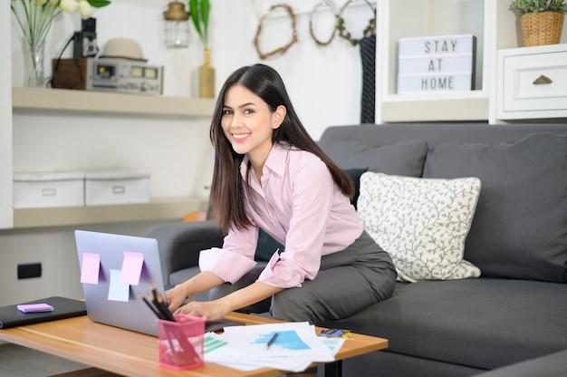 Una mujer de negocios está trabajando con una computadora portátil y está analizando los datos del gráfico de crecimiento empresarial en la sala de estar, trabajo desde casa, concepto de tecnología empresarial.