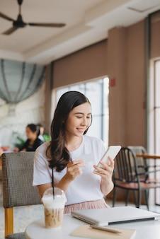 Mujer de negocios trabajando en una computadora portátil y un teléfono, sentado en un café