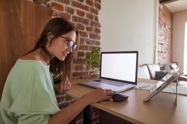 Mujer de negocios trabajando en equipo portátil en casa.