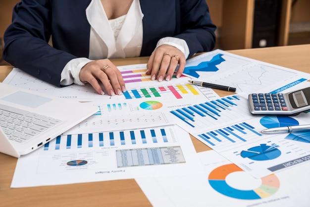 Mujer de negocios trabajando en equipo portátil con gráfico de negocios