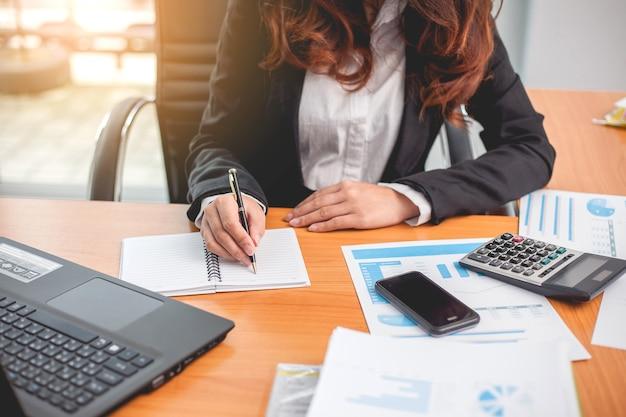 Mujer de negocios trabajando con informes financieros y computadora portátil en la oficina