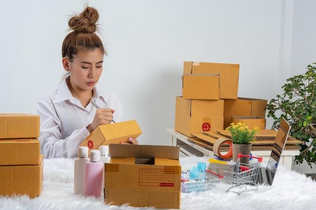 Una mujer de negocios está trabajando en línea y tratando de responder al cliente en el embalaje de la oficina en la pared.